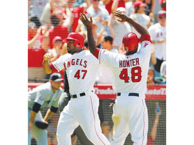 Angels second baseman Howie Kendrick, left, and outfielder Torii Hunter celebrate after scoring against the Seattle Mariners during the eighth inning on Sunday in Anaheim.