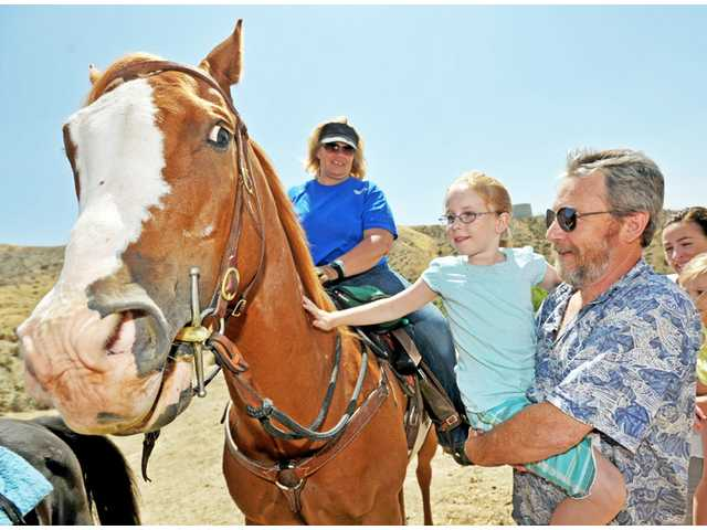 Jim Anderson, of Saugus, holds up Autumn Anderson, 8, as she visits with Mac, ridden by Teresa Spencer of Equestrian Trails, Inc., at the dedication of the Haskell Canyon Open Space in Saugus on Monday.
