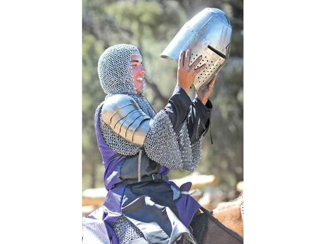 "Chris Burk, ""Sir Christopher of Acton"" puts on his chainmail and helmet as he prepares for the jousting contest."
