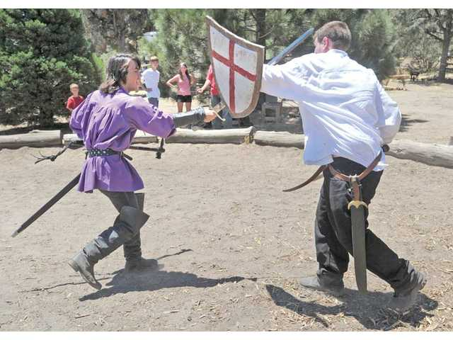 Burk, left, and Taylor Jackson give a sword fighting demonstration.