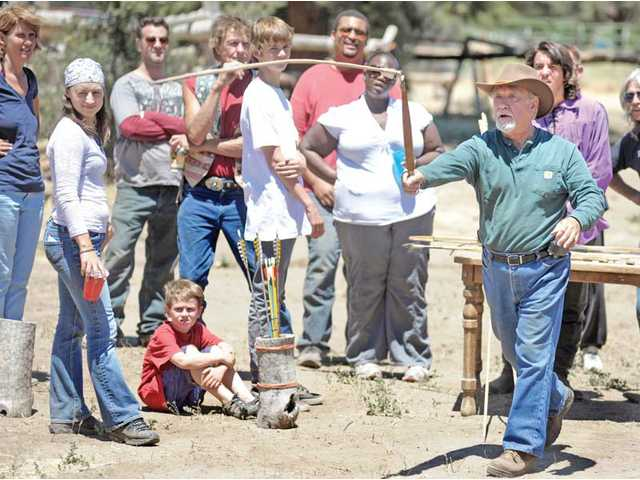 Gary Baugh, right, uses an atlatl, a spear-throwing weapon, to throw a dart at a target as he demonstrates the use of primitive weapons at Zoppeland in Frazier Park on Sunday.