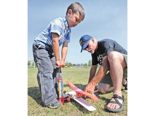 Diego and Dave Cowart, of Castaic, pump up the model airplane.