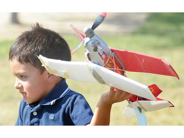 Gabriel Campollo, 4, runs to launch the model airplane.