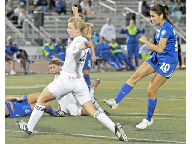 Blue Heat forward Liz Franco, right, shoots past Strikers defender Rachel Flemming and scores the game-tying goal on Wednesday at Canyon High School.