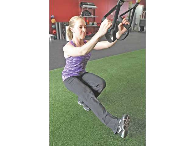 Physical therapist Amy Wunsch, a client at Newhall's Results Fitness gym, demonstrates a single leg squat while utilizing a TRX, which adds an extra strength training element.