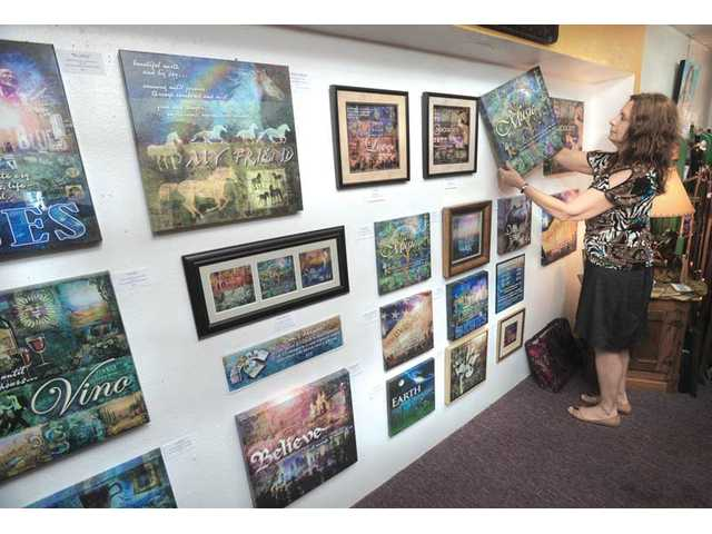 Cook arranges her digital paintings on the artist-display wall at OutWest Marketing in Newhall, where her work is showing until the end of July. Cook, originally from New Jersey, relocated to California in the mid-80s and now calls Canyon Country home.