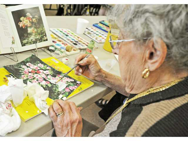 Marina Marcelin, 95, works with acrylic paint during an art class at the Santa Clarita Valley Senior Center in Newhall on Thursday.