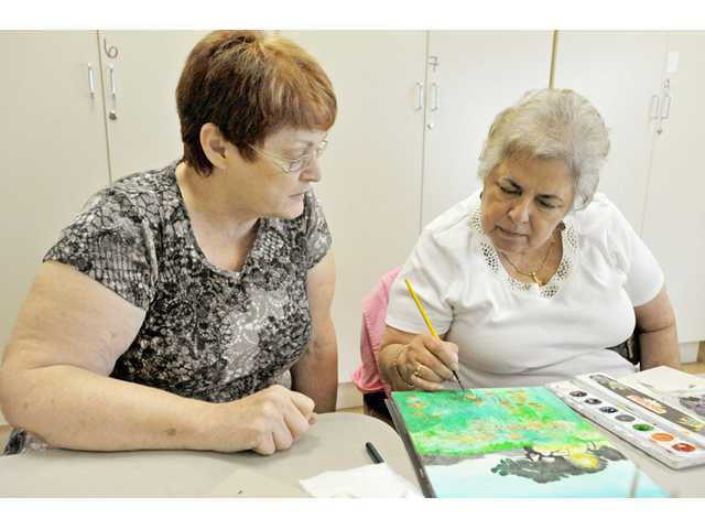 Instructor Peggy Patti watches as Marlene O'Shea, 72, works on a watercolor painting during Patti's art class at the Santa Clarita Valley Senior Center on Thursday.