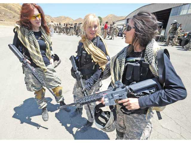 Actresses and models, from left, Sierra Fisk, Amy Johnston, and Lisa Cullen check their military grade Airsoft weapons after participating in war games.