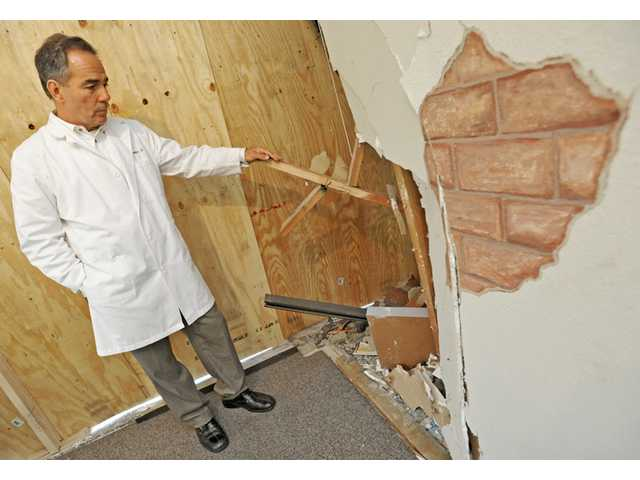 Dr. Karl E. Standifer looks at crash damage done to the storefront of his chiropractic office on Soledad Canyon Road in Saugus.