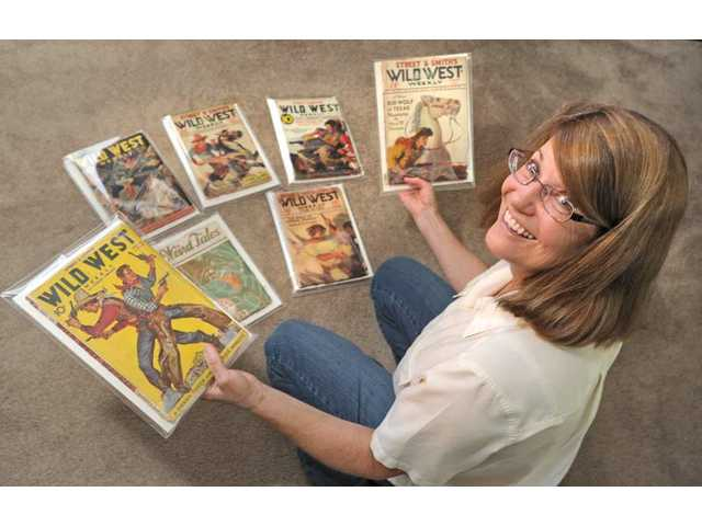 Saugus resident Laurie Powers sorts through pulp-fiction magazines of the 1930s and 1940s. The magazines contain stories written by her grandfather Paul Powers under the pen name of Ward M. Stevens. (