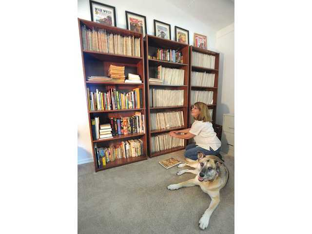 "Powers and her dog Annie sit near a bookshelf displaying a nearly complete collection of pulp fiction magazines from the 1930s and 1940s. The magazines all contain stories written by her grandfather. Powers has written two books about pulp-fiction, ""Pulp Writer: Twenty Years in the American Grub Street"" and ""Riding the Pulp Trail."""