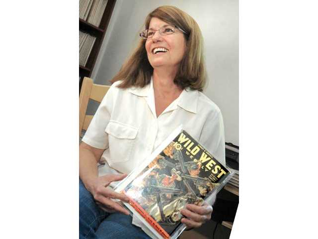 "Powers holds up a copy of Wild West magazine. The magazine, which sold for 10 cents, was one of the many so-called popular ""pulp fiction"" magazines that published fantastic, escapist fiction for the general entertainment of the mass audiences."