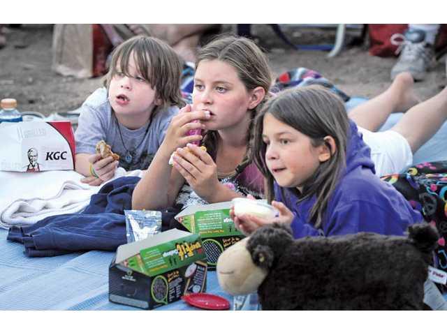 Santa Clarita residents, from left, Burke Battistini, 6, Morgan Gannon, 11, and Maggie Battistini, 11, watch the stage performance.