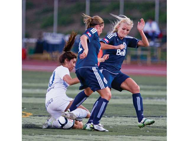 Blue Heat forward Liz Franco tries to secure the ball in a battle with Vancouver Whitecaps players Kelsey Hood, center, and Kaylyn Kyle during Sunday night's W-League playoff game at College of the Canyons. Vancouver won 4-3.