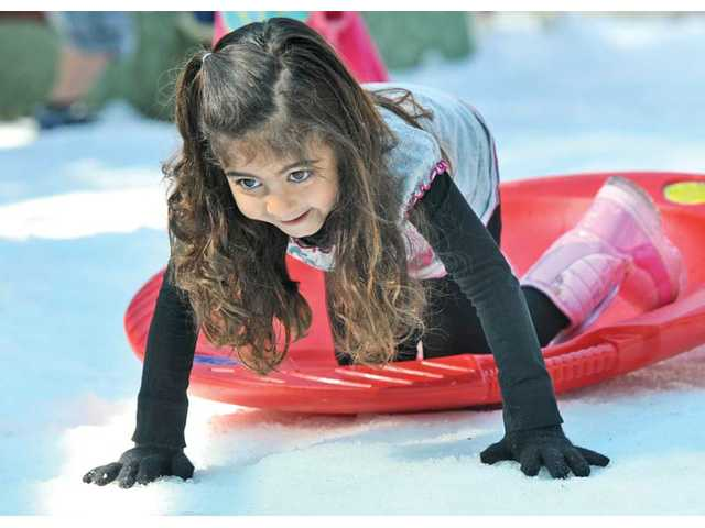 Preschooler Leyla Saifi, 4, wearing gloves and snow boots, scoots her snow disk along a patch of five tons of snow that were dumped on the play yard for the preschoolers at Creative Years Preschool in Santa Clarita on Wednesday.