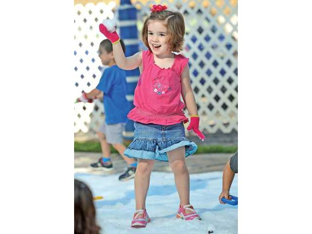 Preschooler Claire Richardi, 4, makes a snow ball on the play yard in Santa Clarita on Wednesday.