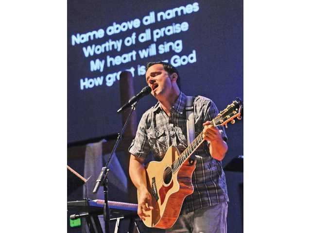 "Lyrics to the song ""How Great is Our God"" are projected on a screen as Aaron Koester on acoustic guitar with One Voice."