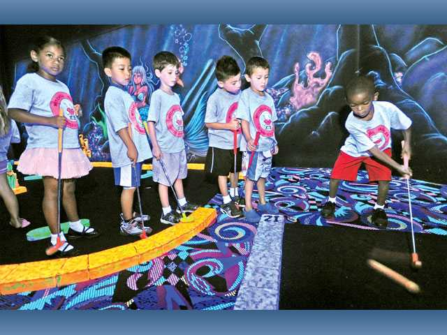 Damarion Davis, 6, right, putts on one of the 18 holes with his 25 kindergarten and first-grade classmates from Mitchell Eagles Summer Camp Fun Club from Canyon Country as they enjoy a round of indoor glow-in-the-dark miniature golf at Fin's Glow Zone in Valencia on Wednesday.