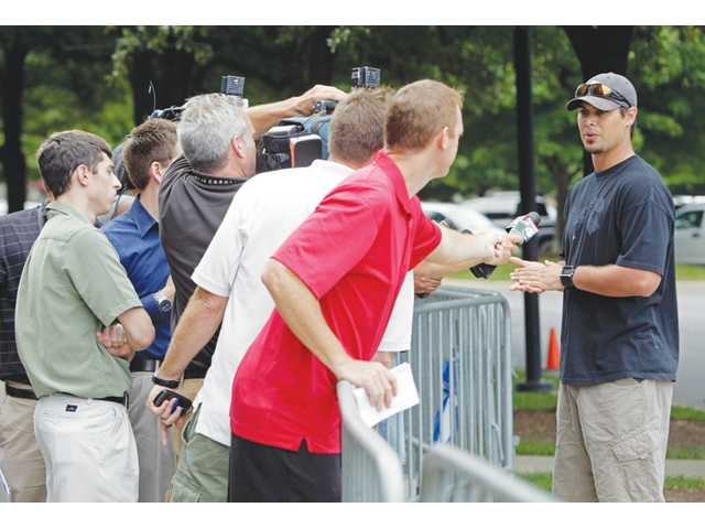 New Miami Dolphins quarterback Matt Moore, right, talks with the media as he arrives at Bank of America Stadium in Charlotte, N.C., Tuesday, the day after the NFL lockout ended.