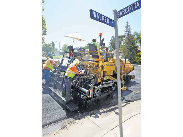 A paver lays down a new layer of hot asphalt at the corner of Walker Court and Barcotta Drive in Saugus on Wednesday as part of the city's street-overlay project.
