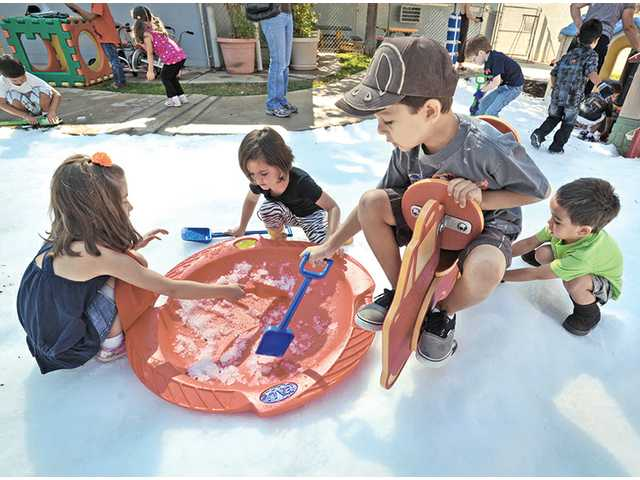 Five and 6-year-olds, from left, Lexi Krainian, Mattea Falino, Diego Salas and Holden Aspiras use tools to gather snow with plans to build a snowman at Creative Years Preschool in Santa Clarita on Wednesday. Five tons of snow was dumped at the preschool.