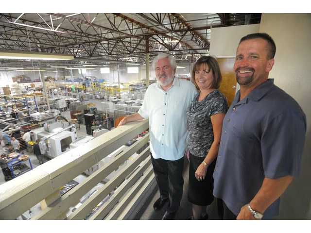 Bayless Engineering and Manufacturing, from left, President Earl Bayless, Controller Andrea McAfee and Vice President Rod Smith stand overlooking the assembly and powder-coating facility in the Valencia Industrial Center on Wednesday.