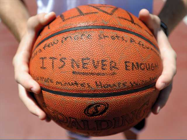 Golden Valley High graduate Taylor Statham holds his practice ball on which he has written inspirational words and phrases.