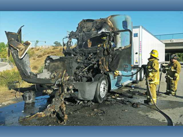 Firefighters clean up after knocking down a fire that consumed the cab of a big rig on the shoulder of northbound Interstate 5, north of Valencia Boulevard, in Valencia on Monday.