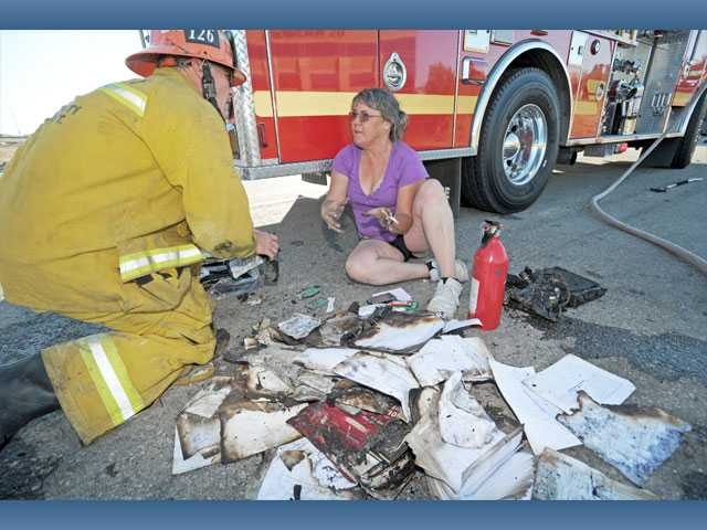 Goulet assists the driver of the truck, who declined to be identified, with her belongings after a fire in her big rig's cab forced her to pull over.