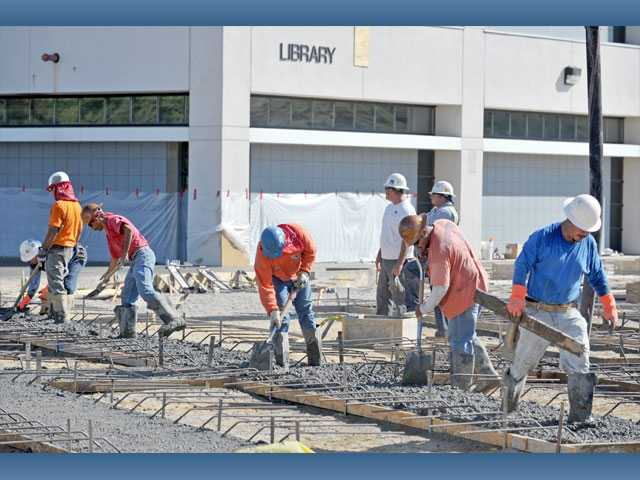 Workers pour and set concrete for the library expansion project at College of the Canyons Valencia campus on Monday.