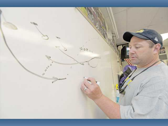 Valencia High School head football coach Larry Muir diagrams a fly left pitch pass, one of the trick plays in his team's arsenal. Trick plays, which have been around for decades, are a good way for not only football teams but teams in all sports to catch opponents off guard and swing momentum.