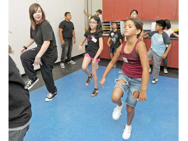 Gabriella Perry, 16, left, leads a warm-up with Gizelle Hernandez, 10, middle, and Ariana Barragan, 9, during a dance class at the Santa Clarita Community Center in Newhall on July 27.