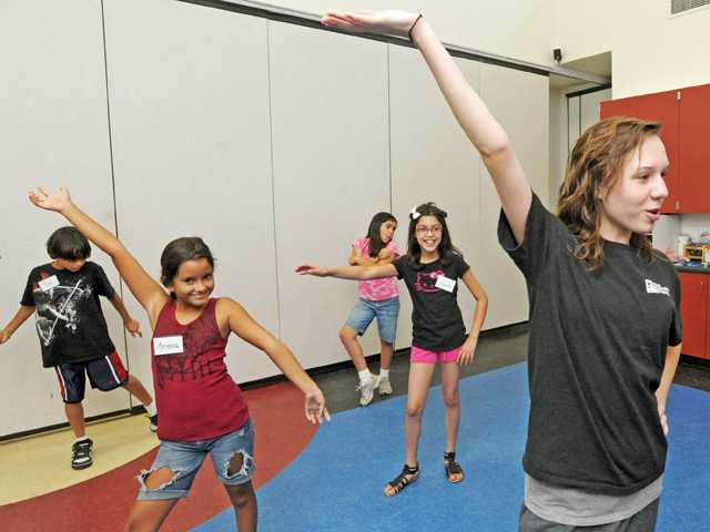 "Marcella Perry, 14, right, strikes a pose as the class learns a routine set to the Taio Cruz song ""Higher."""