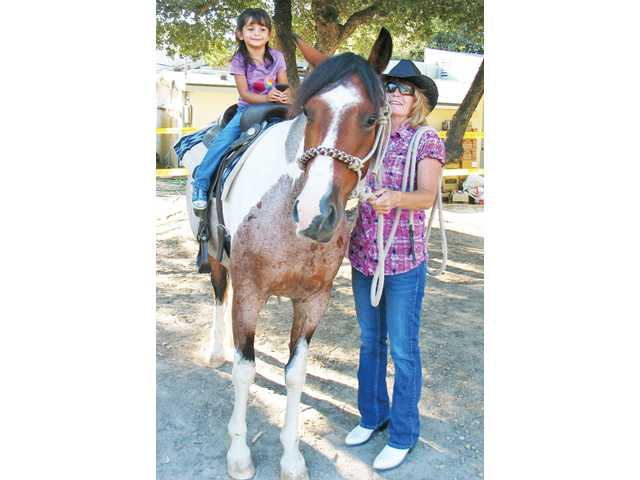 Tina House, of Canyon Country, gives 3-year-old Emily Lizaragga a ride on Durango.