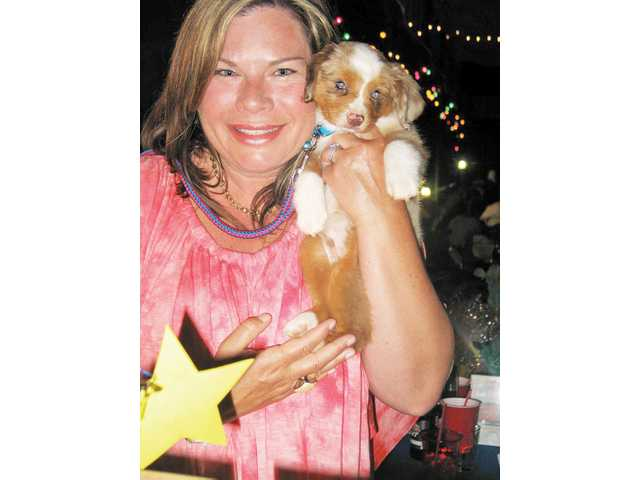 Lisa Ellis, of Channel Islands, won Dexter, the 9-week old toy Australian Shepherd puppy for $600 at the Cops and Cowboys dinner, dance and auction.