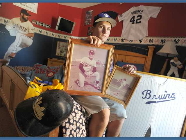 Valencia High pitcher Luke Soroko displays memorabilia of his late father, Mark, who died of a heart attack on March 14, 2010. Soroko pitched four days later and honors his late father with his play.