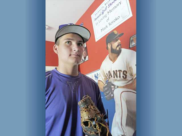 Valencia High pitcher Luke Soroko stands alongside a photo of Giants closer Brian Wilson, his favorite player, and a sign honoring his late father Mark, who died of a heart attack.