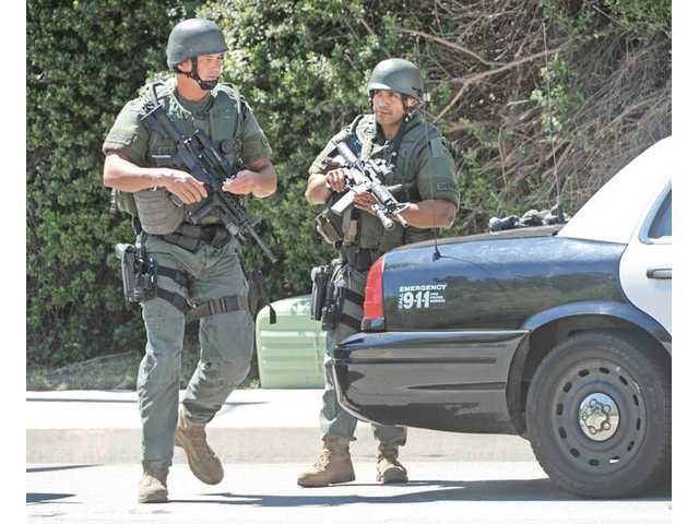 A special-weapons team from the Sheriff's Department's Special Enforcement Bureau prepares its equipment as deputies surround a barricaded suspect in a home near the corner of Zion Court and Olympic Street in Castaic on Wednesday.