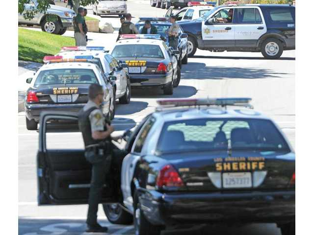 A special-weapons team from the Los Angeles County Sheriff's Department Special Enforcement Bureau move in on a home where a burglary suspect barricaded himself, near the corner of Zion Court and Olympic Street, in Castaic on Wednesday.