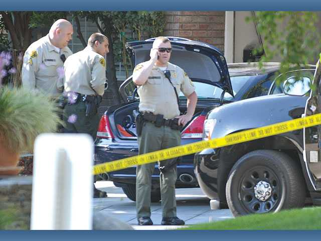Santa Clarita Valley Sheriff's Station deputies secure the area around a dark colored four door sedan where the bodies of three adults were found dead in front of a home on Bay View Court near Bayside Lane in Bridgeport in Valencia on Friday evening.