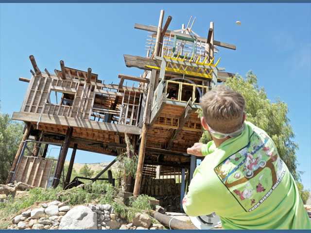 "Noah Fahey, son of ""Phonehenge West"" builder Alan ""Kim"" Fahey, throws a stone at the landmark wooden tower on the Acton property as it is demolished on Friday. See A5 for story and more photos."