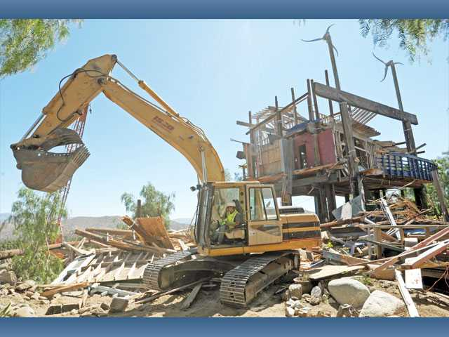 """An excavator, operated by Dennis Panico of Black & White Construction, tears down a section of the landmark wooden tower at """"Phonehenge West"""" in Acton on Friday."""
