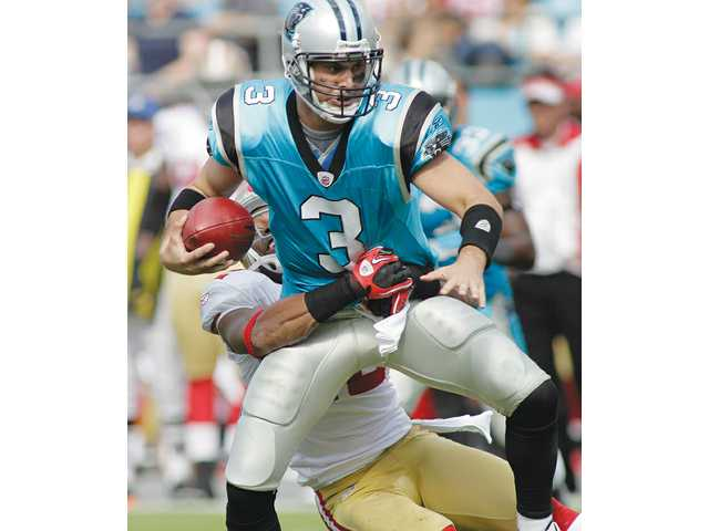 Hart High graduate and former Carolina Panthers quarterback Matt Moore tries to escape the grasp of former 49ers cornerback Nate Clements on Oct. 24, 2010, in Charlotte, N.C. Moore, now a member of the Miami Dolphins, has had ups and downs as an NFL starting quarterback.