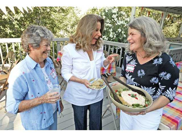 Neighbors Doreen Porter, left, and Doreen Breckenridge, middle, chat with  block party co-hostess Merry Graham as she brings out a taco salad at her Newhall home.