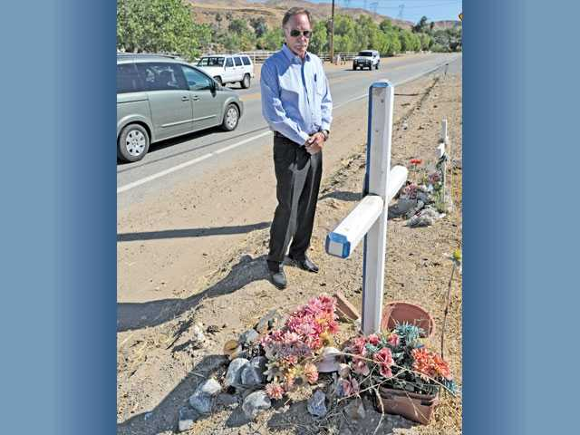 Cars pass by concerned citizen Bob Skerstonas on Friday as he stands near memorial markers on Sierra Highway on a stretch of road in Santa Clarita that has seen many auto-involved fatalities.