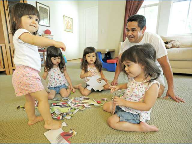 German Gonzalez, a former auto dealership-service adviser, has been a stay-at-home dad to daughters, from left to right, Sarah, 19 months, and triplets Claire, Kate and Jamie, who are almost 3.