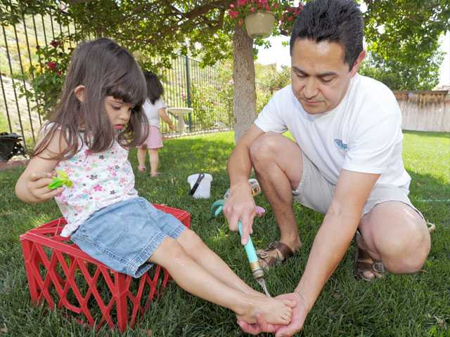 Gonzalez cleans Claire's feet after she spends time in the sandbox, located in the family's backyard.