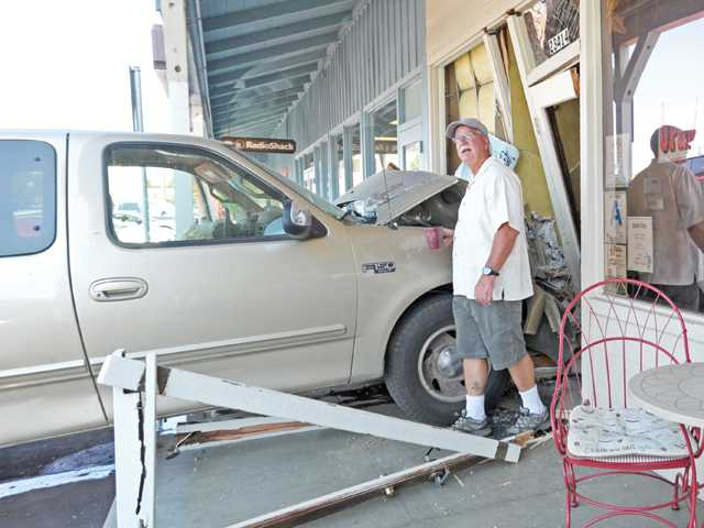 Owner Mark David walks out and surveys the scene where a Ford F-150 pickup truck crashed through the storefront of The Coffee House in Newhall on Thursday.
