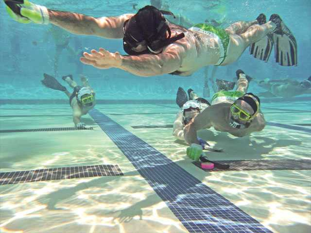 Tyler Dobelbower, top, goes out for a pass from Bill Walker, lower-right, during an underwater hockey game at the Santa Clarita Aquatic Center. The sport has been played in the Santa Clarita Valley for more than two decades. The game involves 10 total players, with six at once in the water.